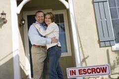 Pares que abraçam em Front Of New House Foto de Stock