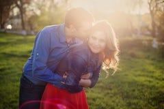 Pares que abraçam no parque no por do sol Imagem de Stock