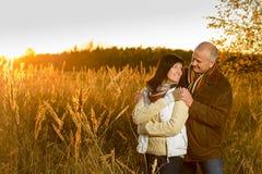 Pares que abrazan durante campo de la puesta del sol del otoño Imagen de archivo