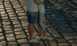 Pares que abrazan en el camino del guijarro en la puesta del sol Fotos de archivo