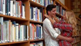 Pares que abrazan en la biblioteca almacen de metraje de vídeo