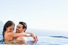 Pares que abrazan en la piscina Imágenes de archivo libres de regalías