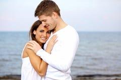 Pares que abrazan en la playa que parece feliz Foto de archivo
