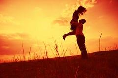 Pares que abrazan en la puesta del sol Fotos de archivo libres de regalías