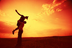Pares que abrazan en la puesta del sol Fotografía de archivo libre de regalías