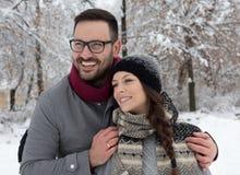 Pares que abrazan en nieve fotos de archivo
