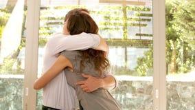 Pares que abrazan en nuevo hogar