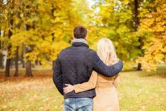 Pares que abrazan en parque del otoño de la parte posterior Imágenes de archivo libres de regalías