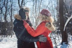 Pares que abrazan estando en amor en un día de invierno frío en la nieve imagenes de archivo