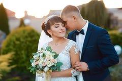 Pares que abrazan, la novia de la boda que sostiene un ramo de flores en su mano, el novio que la abraza foto de archivo libre de regalías