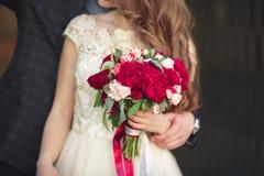 Pares que abrazan, la novia de la boda que sostiene un ramo de flores en su mano, abarcamiento del novio Imágenes de archivo libres de regalías
