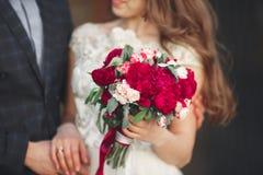 Pares que abrazan, la novia de la boda que sostiene un ramo de flores en su mano, abarcamiento del novio Fotos de archivo