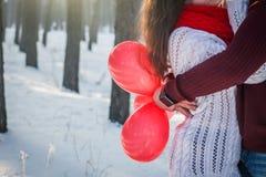 Pares que abrazan llevando a cabo el manojo de baloons Fotografía de archivo libre de regalías