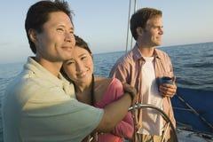 Pares que abrazan por el amigo en el velero Imagen de archivo libre de regalías