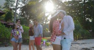 Pares que abrazan sobre el baile del grupo de la gente en hombres felices y mujeres del parque tropical de la palmera el vacacion almacen de video