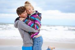 Pares que abrazan y que se divierten en la playa Fotografía de archivo