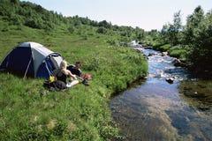 Pares que acampam ao lado do córrego Imagem de Stock Royalty Free
