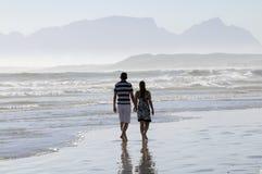 Pares que andam ao longo da praia em África do Sul imagens de stock royalty free