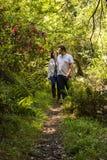 Pares que andam através de um jardim da mola Foto de Stock Royalty Free