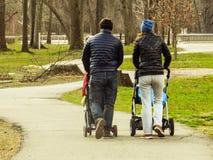 Pares que andam com carrinhos de criança de bebê através de um trajeto em um parque fotos de stock