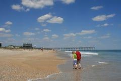 Pares que andam com os pés descalços na praia Fotografia de Stock