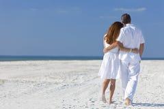 Pares que andam em uma praia vazia Imagens de Stock Royalty Free