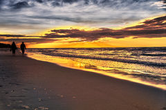 Pares que andam na praia no por do sol Foto de Stock