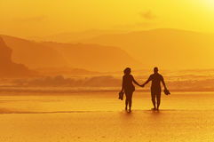 Pares que andam na praia no por do sol Foto de Stock Royalty Free