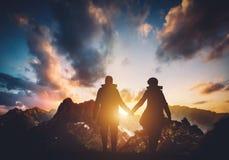 Pares que andam nas montanhas durante o por do sol imagem de stock
