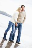Pares que andam no sorriso das mãos da terra arrendada da praia Imagem de Stock Royalty Free