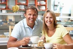 Pares que apreciam a fatia de bolo e de café no café Imagens de Stock