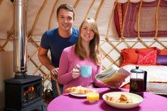 Pares que apreciam o café da manhã que acampa em Yurt tradicional Fotos de Stock Royalty Free