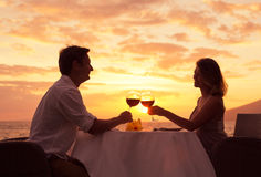 Pares que apreciam o jantar romântico do sunnset Imagem de Stock