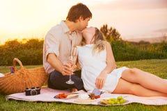 Pares que apreciam o piquenique romântico do por do sol Imagens de Stock
