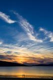 Pares que apreciam o por do sol lindo na praia Luskentyre, ilha de Harris, Escócia Imagem de Stock