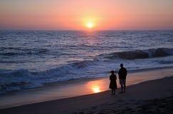 Pares que apreciam o por do sol na praia de Aliso fotos de stock royalty free