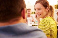 Pares que apreciam a refeição exterior do verão com amigos Imagens de Stock Royalty Free