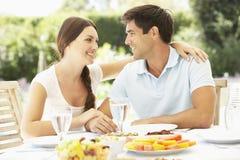Pares que apreciam a refeição exterior no jardim Fotos de Stock Royalty Free