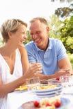 Pares que apreciam a refeição no jardim Fotos de Stock Royalty Free