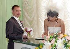 pares que assinam o registo do casamento Fotografia de Stock