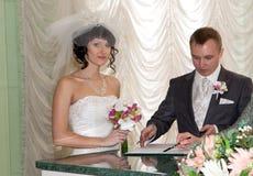 Pares que assinam o registo do casamento Imagem de Stock