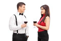 Pares que beben el vino rojo y que hablan el uno al otro Fotos de archivo libres de regalías