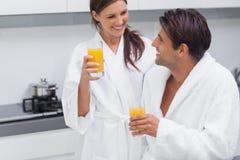 Pares que beben el zumo de naranja Fotos de archivo