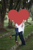 Pares que beijam atrás do entalhe do coração Foto de Stock Royalty Free