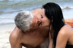 Pares que beijam na praia imagem de stock