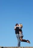 Pares que beijam sob o céu imagem de stock