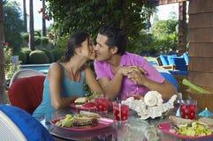 Pares que beijam sobre a refeição na tabela exterior Foto de Stock