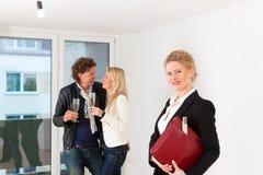 Pares que buscan las propiedades inmobiliarias con agente inmobiliario femenino Imágenes de archivo libres de regalías