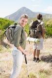 Pares que caminan atractivos que caminan en la mujer del rastro de montaña que sonríe en la cámara Fotos de archivo libres de regalías