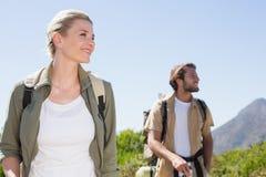 Pares que caminan atractivos que caminan en rastro de montaña Imagen de archivo libre de regalías